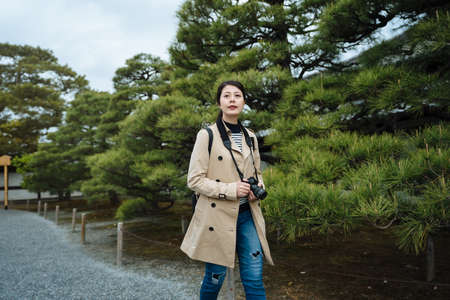 smiling chinese photographer walking along pine trees is visiting a japanese style garden. asian lady holding camera is strolling on path surrounded by plants and enjoying the fresh air.