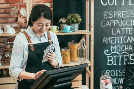 startup business successful and money concept. young woman cafe owner with dollar cash money counting earn of coffee shop on point of sale terminal machine. lady waitress laughing account on tablet. Archivio Fotografico
