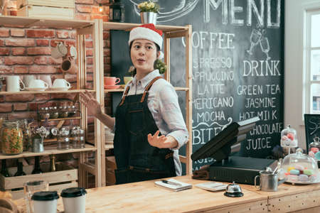 cheerful asian korean woman in red santa hat celebrating xmas holidays event in bar counter. carefree female waitress in cute decor on head dancing and having fun in coffee shop while working. Archivio Fotografico