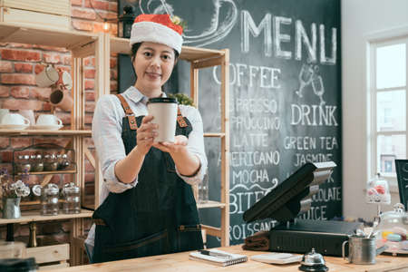 attractive young waitress smiling and holding paper to-go cup of coffee showing to camera. friendly girl bartender in santa hat giving take away drink of customer order. merry xmas holidays concept. Archivio Fotografico