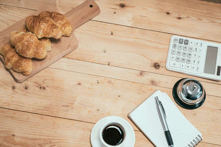 Close-up top view of cup of espresso and crispy croissant on wooden table. delicious handmade bread in coffeehouse. calculator and note for counting finance of cafe store by serving bell indoors.