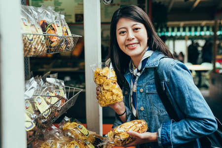 female travel blogger is showing a bag of dried fruit in front of camera. pretty korean woman buying healthy snacks from metal rack is smiling. Archivio Fotografico