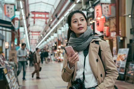 Minami Namba and Shinsaibashi. female tourist standing in local market and searching fresh seafood shop at daytime. young girl carrying camera and holding smartphone look japanese local lifestyle Archivio Fotografico