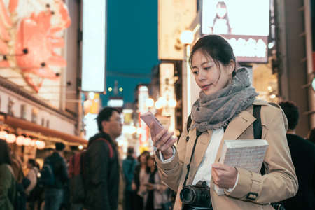 female tourist walking in night shopping street at Dotonbori. young girl photographer holding guide book standing in famous destination for traveler in Osaka japan. woman looking at smartphone screen Archivio Fotografico