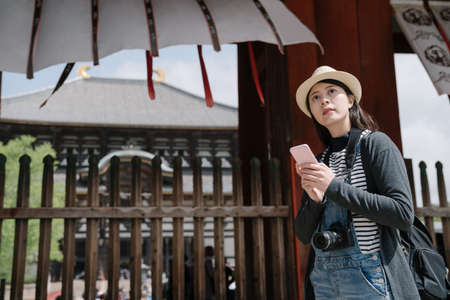 asian backpacker near the entrance of temple is using navigation apps on smartphone. girl holding mobile is looking into distance background streamers fluttering in breeze Archivio Fotografico