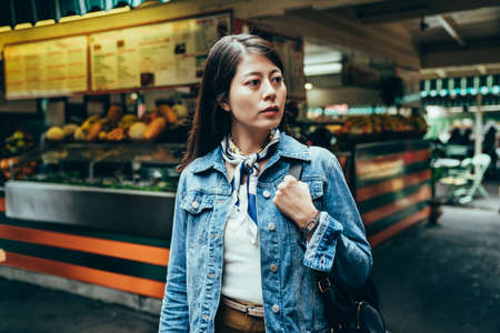 asian woman is thinking about where to head to next in front of a juice bar. female backpacker looking away just finishing visiting local traditional market, going to leave.