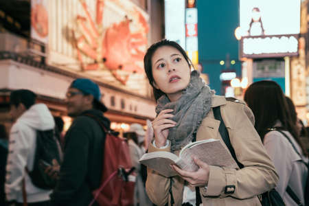 Shopping young girl reading guidebook in modern urban. Beautiful woman having fun in city in dotonbori. female tourist standing in crowded searching direction on map in travel book at night city.