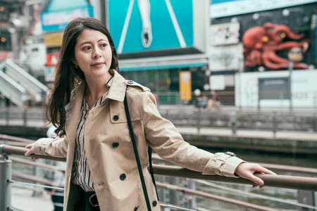 Portrait of Asian woman smiling and relaxing on bridge by canal. young happy girl wearing coat looking aside and enjoy sunshine by river in dotonbori and shinsaibashi in osaka. famous blue billboard.