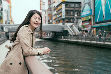 Pretty woman with makeup enjoying city view from bridge in spring day. Lovely chinese woman in jacket spending time outdoors under bright sunny sky. travel japan in famous dotonbori and shinsaibashi