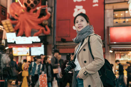 red octopus sign seen at Dotonbori street Namba. side view of elegant smiling young girl tourist walking on night city street holding professional camera. female backpacker curiously sightseeing. Archivio Fotografico