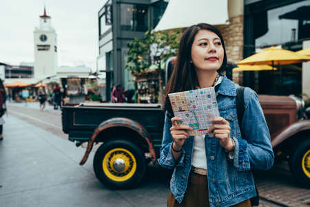 asian girl studying abroad holding map is looking at the surroundings by pickup truck. female exchange student looking forward to exploring new places and trying new things. authentic lifestyle