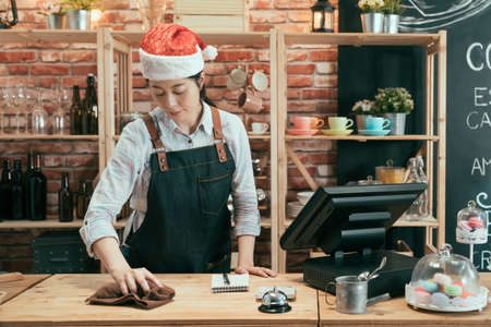 elegant female cafe worker wipes wooden counter table in cafeteria. coffee shop celebrating christmas holidays. asian chinese woman wear apron and xmas santa hat cleaning up in coffeehouse in winter