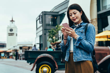 blurred background smiling girl traveling independently is using mobile on the street. young woman standing and looking up information on the internet with phone. authentic lifestyle Archivio Fotografico