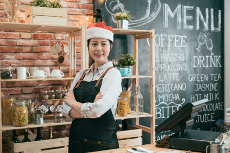 confident pretty asian female waitress in apron and xmas santa hat crossed arms face camera smiling. charming girl barista celebrating christmas holidays with coffee shop bargain sale waiting client