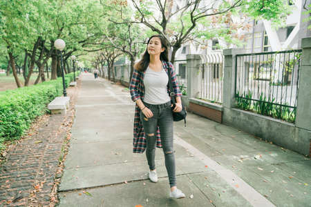 full length young beautiful trendy asian korean girl in long shirt and jeans walking in pathway in park. attractive woman looking aside while carrying backpack. cute female relax outdoor sunny day.