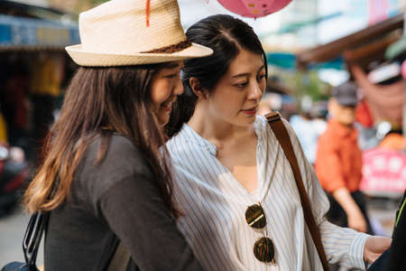 Charming female friends having fun choose new dress to buy at clothing vendor in local market in bangkok thailand. Beautiful women shopping outdoor sunset time. Friendship travele lifestyle concept
