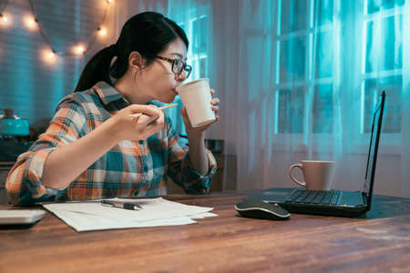 side view of young asian japanese elegant housewife counting finance in dark night home kitchen and eating tasty instant noodles. lady drink ramen soup as bedtime snack while looking at laptop screen