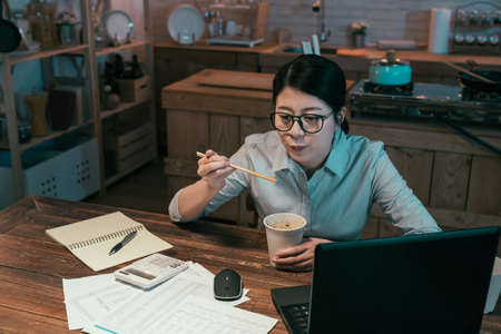 Young serious businesswoman eating chinese food from disposable paper cup and smiling enjoy sitting at wooden dining table in dark kitchen. beautiful lady worker enjoy ramen soup during overtime work Archivio Fotografico