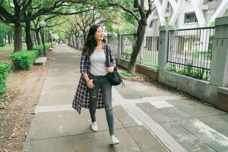 full length beautiful Asian korean woman walking fast on pathway in park Barcelona Spain. elegant college girl student with backpack going to school in hurry. smiling lady looking aside outdoors.
