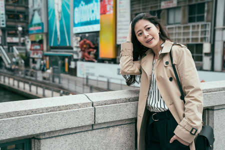 happy carefree young asian woman wearing spring coat standing on bridge. smiling elegant girl with one hand in pocket flicks hair relaxing above river. blurred view of billboards area in background Archivio Fotografico