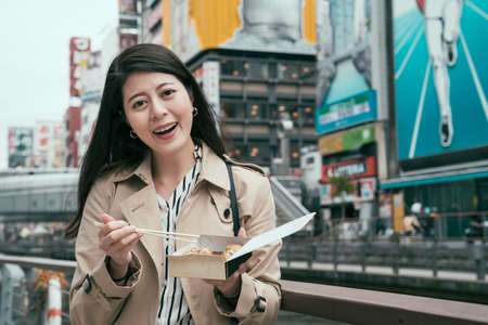 japanese girl worker holding tasty takoyaki in dotonbori near river in osaka japan. young office lady face camera enjoy local street food outdoor by canal. female using chopsticks with lunch box. Archivio Fotografico