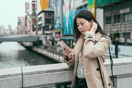 Young asian chinese woman travel in Osaka japan wearing jacket standing by river text on smartphone. dotonbori and shinsaibashi advertisement billboard area in background elegant girl using cellphone