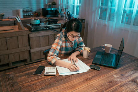 college girl student stay up late sitting at table in dark home kitchen at night. young asian korean woman enjoy cup of instant noodles doing homework and preparing for exam with laptop computer.