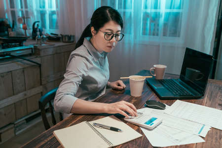 young elegant asian korean businesswoman counting finance of company on calculator with laptop computer and document papers on table in home kitchen. office lady enjoy instant noodles during working