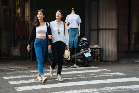 two millennial girlfriends holding hands and laughing across pedestrian crossing. full length asian charming sisters looking same side checking with cars and traffic walking on zebra road outdoors.
