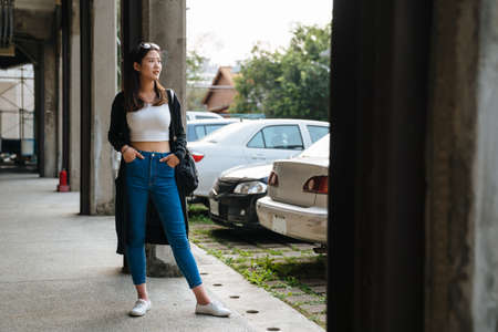 young stylish sexy girl in sunglasse with hands in jeans pockets standing outdoor urban parking lot. hipster casual style female looking aside. full length beautiful lady patiently waiting in walkway
