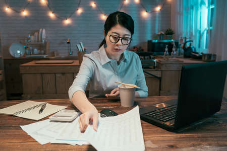 hardworking confident young office lady sitting at home office in kitchen working with deadline project in midnight. female worker in glasses eating instant noodles in cup with chopsticks read papers