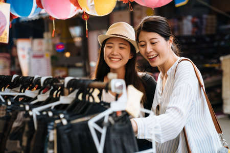 two asian japanese young women friends buying clothes in local market in taiwan taipei. smiling girls sisters having fun choosing products on cloth rack outdoors vendor. female travelers laughing.