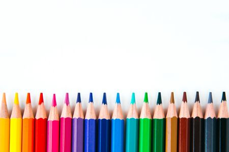 bright multi-colored flat lay pencils for drawing on a white background, place for text