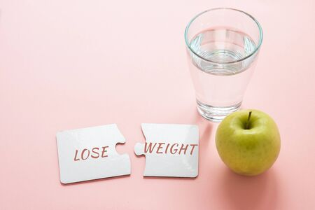 two white disconnected puzzles with the inscription lose weight, a glass of water and a green apple on a pink background, diet concept