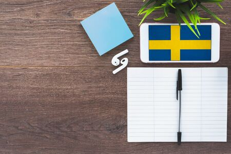 Sweden flag smartphone, wireless headphones, notepad, green plant on brown desktop, place for text