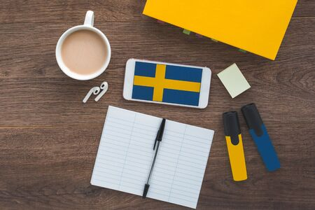 Swedish flag, textbook, smartphone, wireless headphones foreign language learning concept