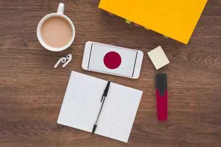 Japan flag, notebook, textbook, smartphone and wireless headphones on a wooden desktop, concept of learning a foreign language