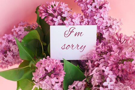 inscription I am sorry on a white gift card in a beautiful spring bouquet of lilac flowers