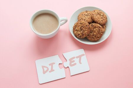 two white disconnected puzzles with the inscription diet, a cup of coffee and a plate with cookies