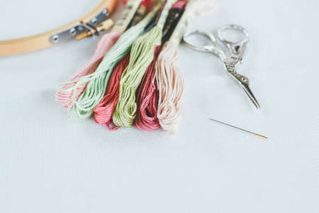 multi-colored cotton floss thread for cross-stitch, a needle, scissors and a wooden hoop on a white canvas 1