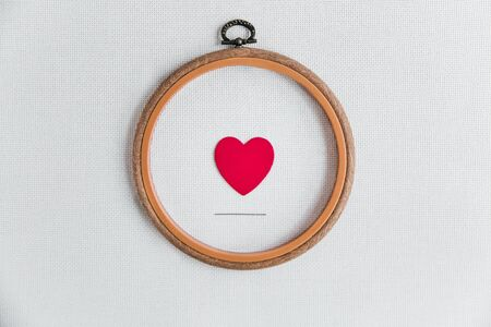 flat lay love for cross-stitch: a red heart in a wooden hoop, a needle on a white canvas aida 16 counts