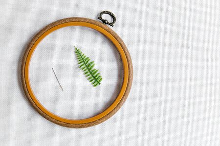 minimalistic flat lay on cross-stitch: a wooden hoop, a needle and a fern branch on a white canvas aida 16 points