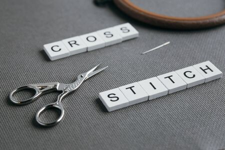flat lay embroidery cross on a gray canvas aida inscription cross-stitch, wooden hoop, needle and vintage scissors for needlework Banco de Imagens