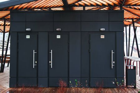 three black public toilet doors on the street