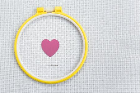 flat lay love for cross-stitch: a pink heart in a yellow hoop, a needle on a white canvas aida 16 counts Banco de Imagens