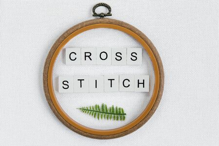 minimalistic flat lay: a wooden hoop, the inscription cross stitch and a sprig of fern on a white canvas aida 16 count