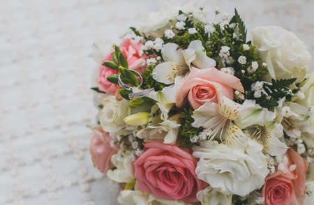bridal bouquet, white gold wedding rings on flowers