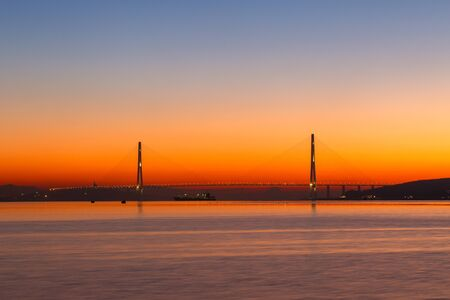Dawn in the sea city of Vladivostok. Cable-stayed Russian bridge over Vostochny Bosphorus Strait to the Russky Island in Vladivostok against the background of a golden dawn during calm sea. 스톡 콘텐츠