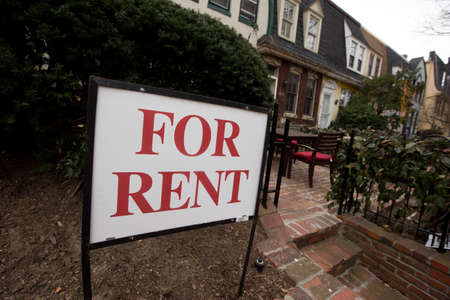 Close-up. A Pho Rent sign is glued to a fence in front of a residential building in downtown Washington DC