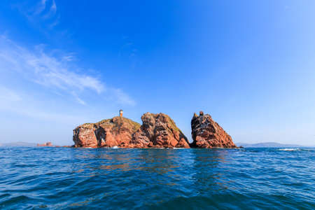 A picturesque red stone island sticks out of the blue sea water. An uninhabited rocky island in the middle of the blue sea against the backdrop of a clear sky Stock Photo